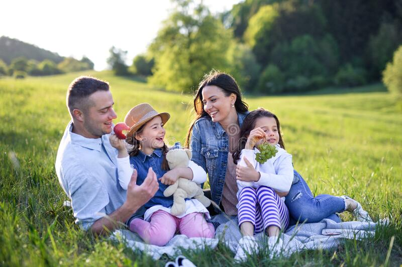 Happy family with two small daughters sitting outdoors in spring nature, having picnic. stock image