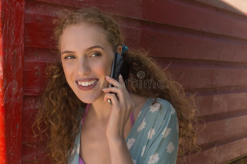 Young Caucasian woman talking to mobile phone at beach hut stock photography