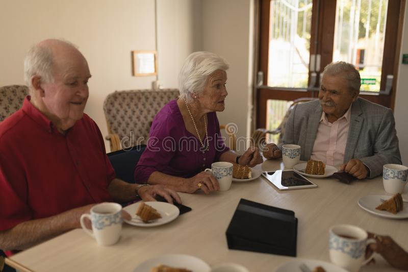 Front view of happy group of senior friends having breakfast on dining table. At home royalty free stock photo
