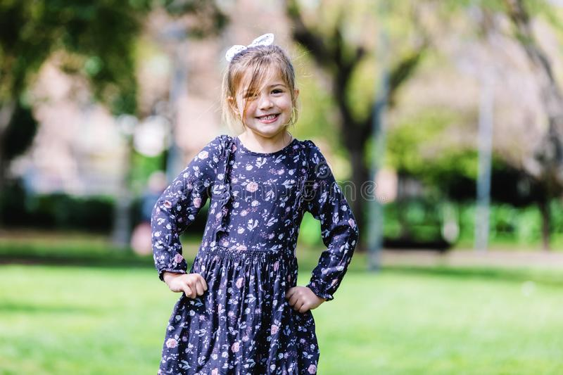 Front view of happy little girl in dress standing in the park royalty free stock images