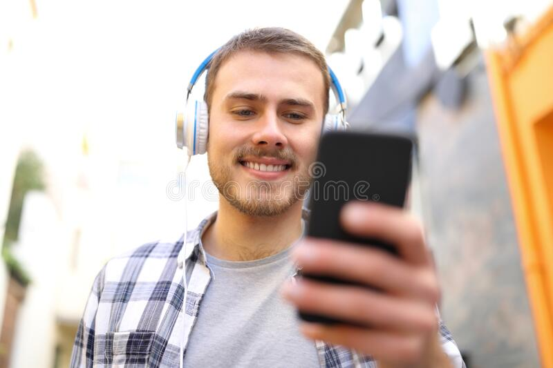 Front view of happy man listening to music walking in the street stock image