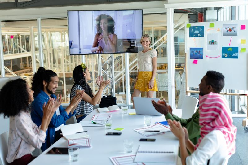 Business people applauding during video conference at conference room in a modern office. Front view of happy Mixed-race business people applauding during video stock image