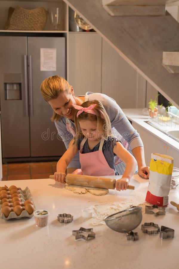 Mother with her daughter preparing food in kitchen. Front view of happy mother with her daughter preparing cookie dough in kitchen at home royalty free stock images