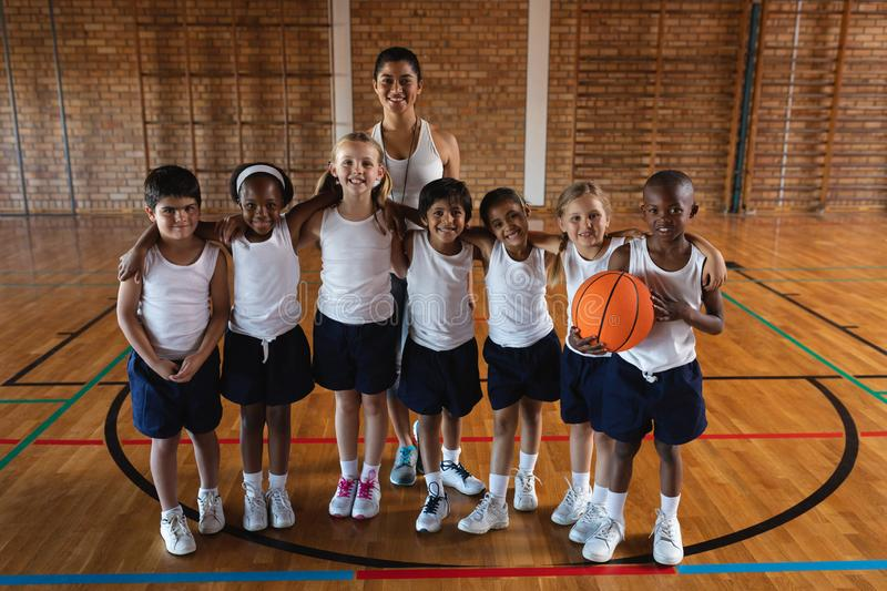 Happy schoolkids and female coach looking at camera at basketball court. Front view of happy schoolkids and female coach looking at camera at basketball court in royalty free stock photography