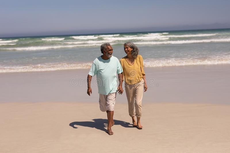 Senior couple holding hands and walking on beach. Front view of happy senior couple holding hands and walking on beach in the sunshine royalty free stock images