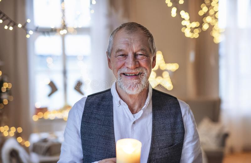 Front view of happy senior man indoors holding candle at Christmas. stock photos