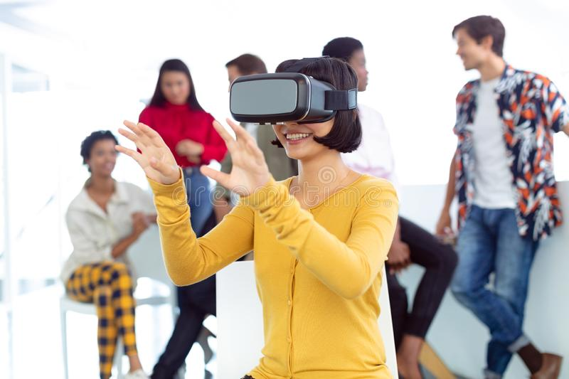 Young businesswoman using virtual reality headset in a modern office. Front view of happy young Caucasian businesswoman using virtual reality headset in a modern stock photography