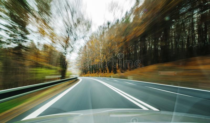 Front view of the highway road passing the country side inside the fast car long exposure shoot stock photo