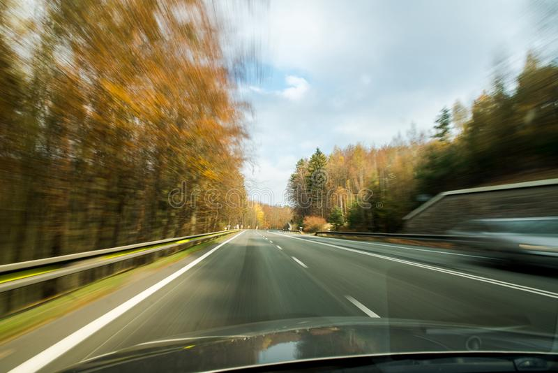 Front view of the highway road passing the country side inside the fast car long exposure shoot stock images