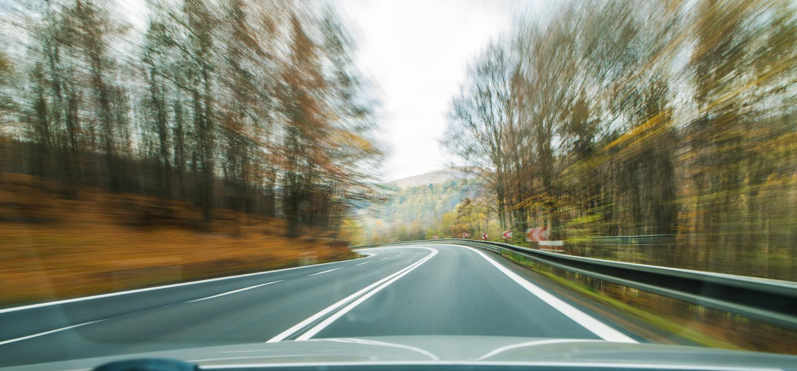 Front view of the highway road passing the country side inside the fast car long exposure shoot royalty free stock photo