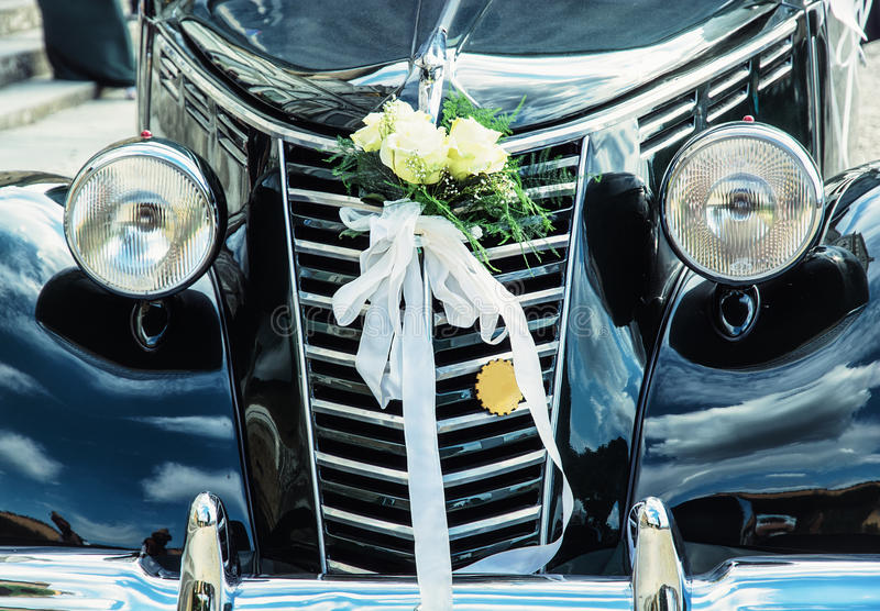 Front view of historical wedding car with ribbon and flowers. Symbol of love royalty free stock image