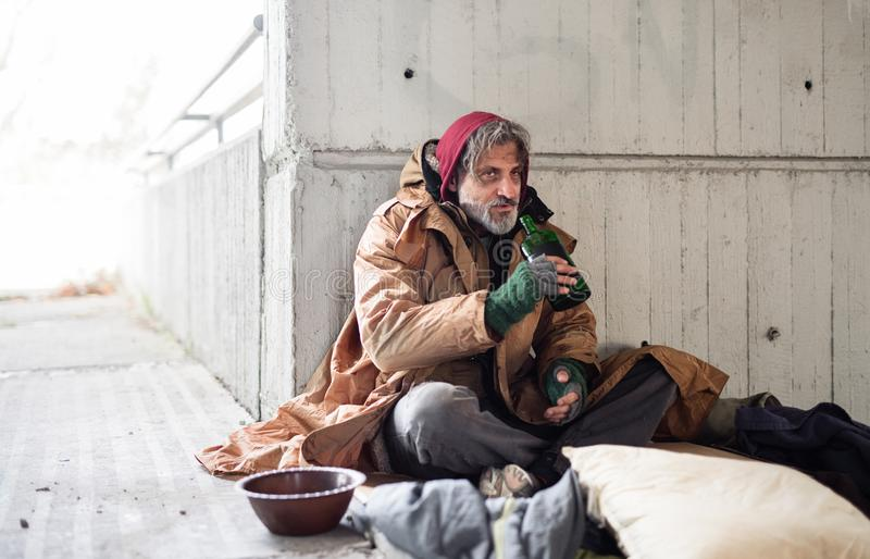 A front view of homeless beggar man sitting outdoors, holding bottle of alcohol. Copy space. stock photo
