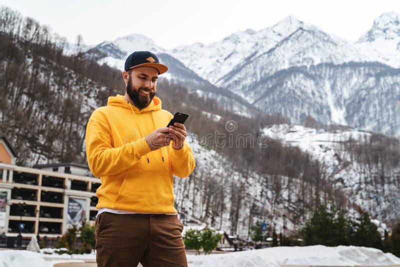 Front View _homme touriste dans jaune hoodie, chapeau tenir sur fond haut neigeux montagne et employer smartphone lifestyle photo libre de droits