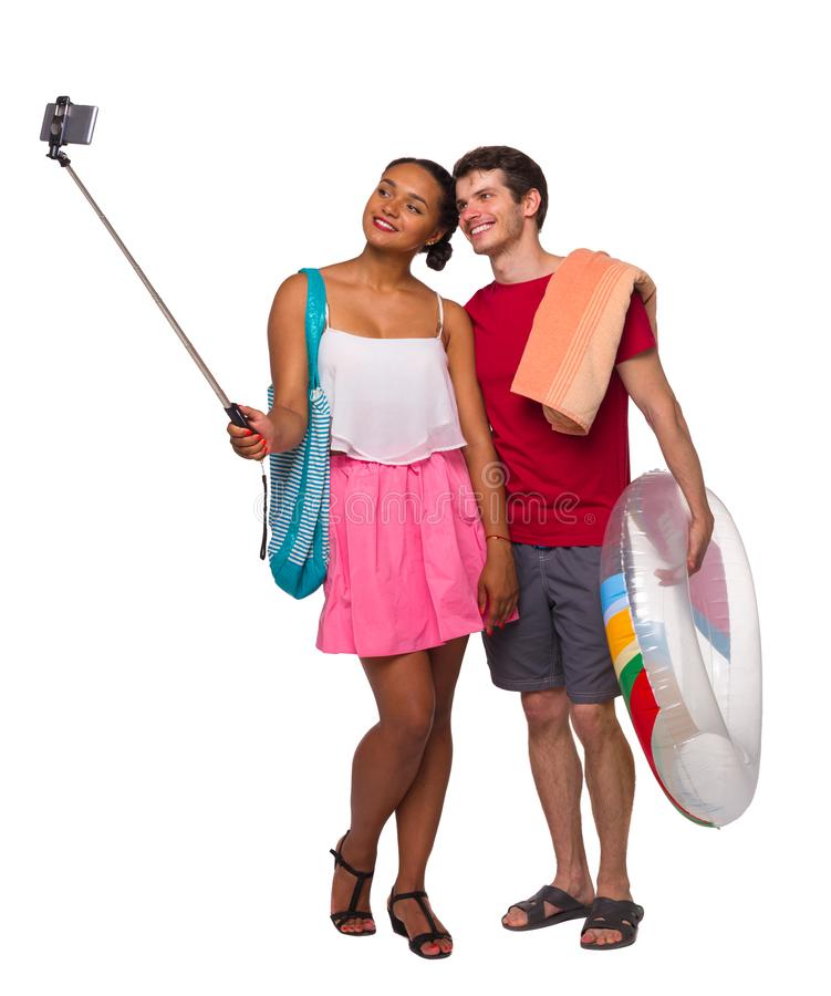 Front view of a an international couple that makes selfie on selfie stick with an inflatable circle and beach accessories stock photo