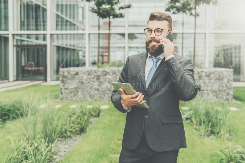Front View Junger glücklicher Geschäftsmann im Anzug und in der Bindung steht im Freien, hält Tablet-Computer und spricht auf sei stockfoto