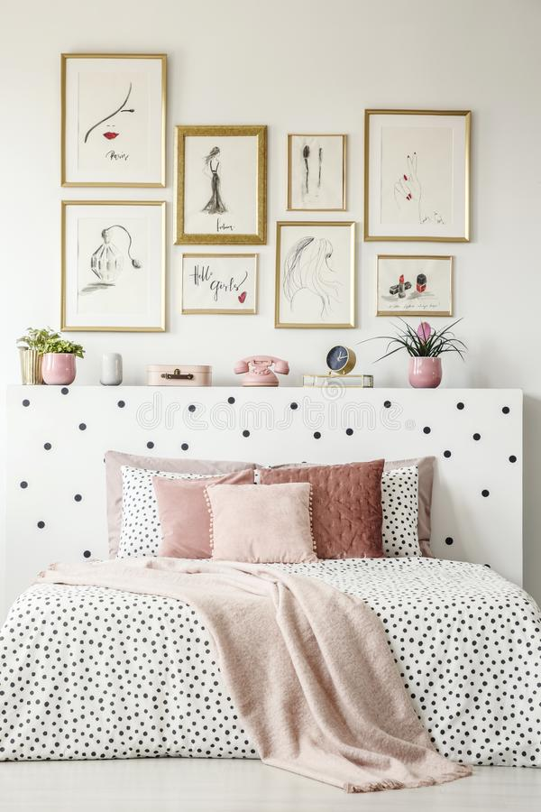 Front view of a king size bed with pink pillows, dotted sheets,. Headrest with decorations and paintings on the wall in a bedroom interior royalty free stock photo