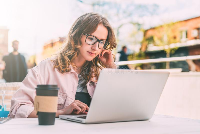 Front View La mujer joven en vidrios se está sentando en la tabla en café de la calle y está utilizando el ordenador portátil Emp imágenes de archivo libres de regalías