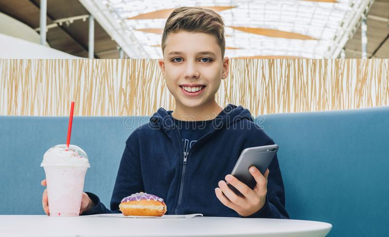Teenager boy sits at table in cafe, drinks milkshake, eats donut, holds smartphone in his hand. Boy plays mobile games. Front view. Laughing teenager boy sits stock photos