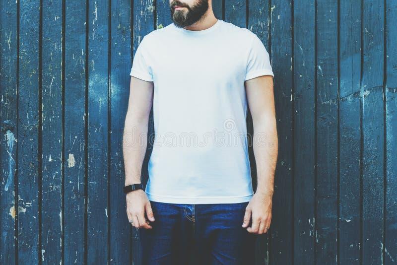 Front View Le jeune homme barbu de hippie habillé dans le T-shirt et des lunettes de soleil blancs est des positions contre le mu image stock