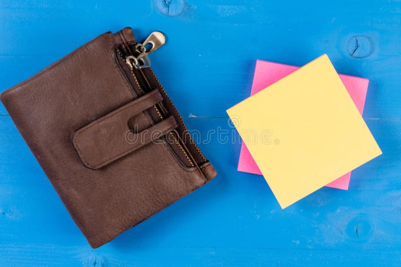Front view leather coin purse wallet colored sticky notes pad wooden background. Reminder notes. Organize things to do royalty free stock photography