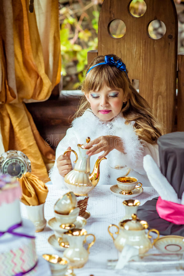 Front view of an little beautiful girl in the scenery of Alice in Wonderland pouring tea into a cup at the table royalty free stock images