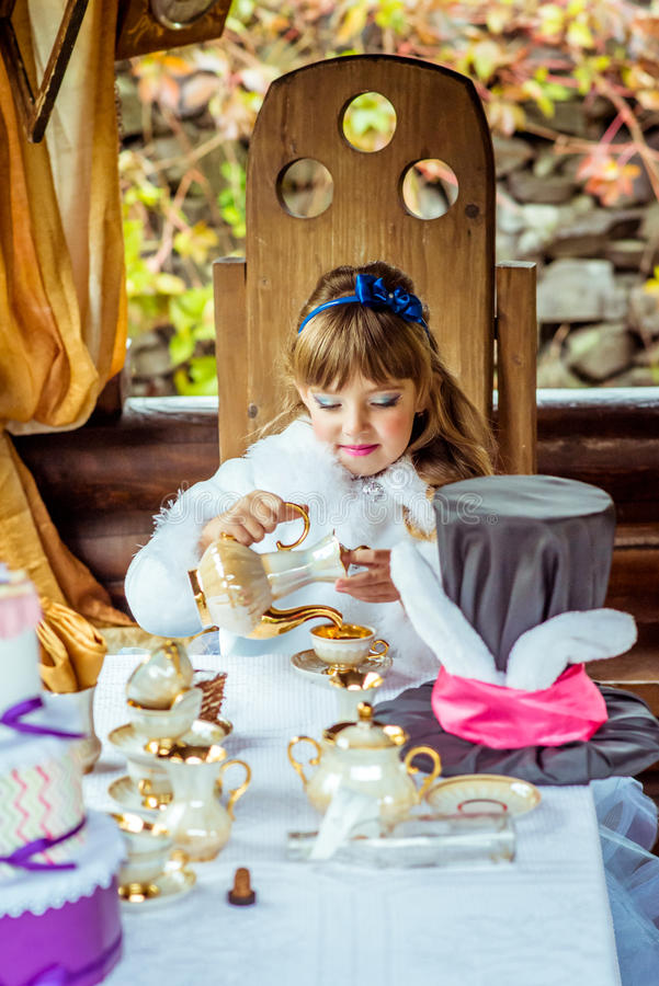 Front view of an little beautiful girl in the scenery of Alice in Wonderland pouring tea into a cup at the table stock photos