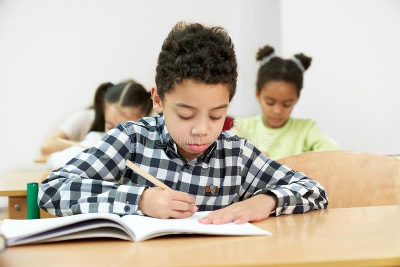 Front view of little boy in process of doing test at school. Front view of little african boy in process of doing test at school. Concentrated male student stock image