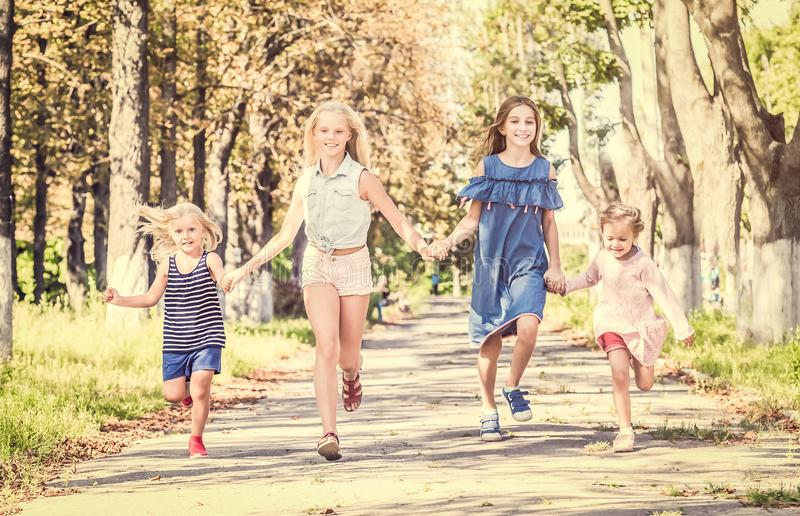 Little smiling girls running on the sunshine autumn alley by holding hands royalty free stock images