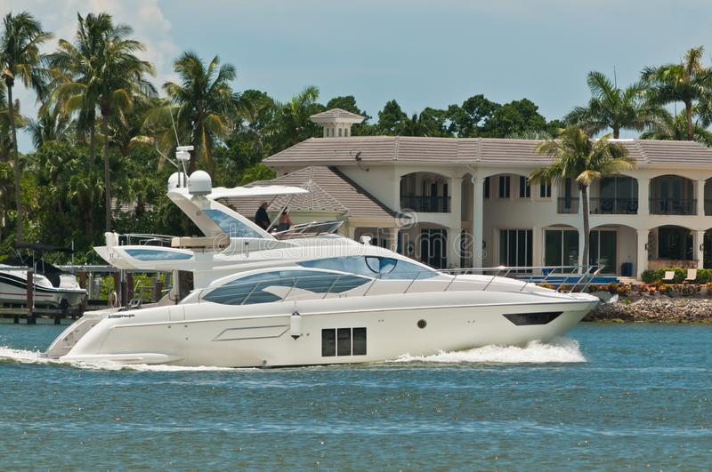 Luxury powerboat cruising tropical canal and condominiums stock image