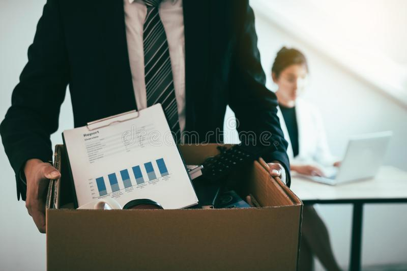 Front view with the male employee standing holding office supplies in the paper box going to submit a resignation letter while a. Female employee is working stock photos