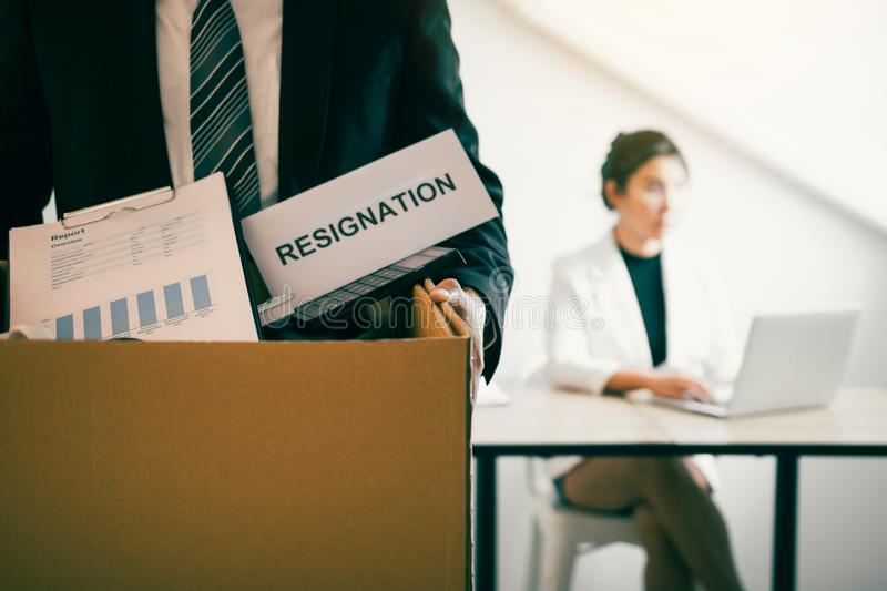 Front view with the male employee standing holding office supplies in the paper box going to submit a resignation letter while a. Female employee is working royalty free stock photo