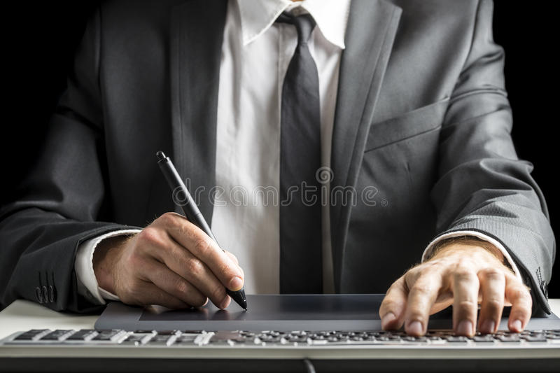 Front view of male graphic designer sitting at his office desk. Front view of male graphic designer or photographer in an elegant suit sitting at his office desk royalty free stock photography