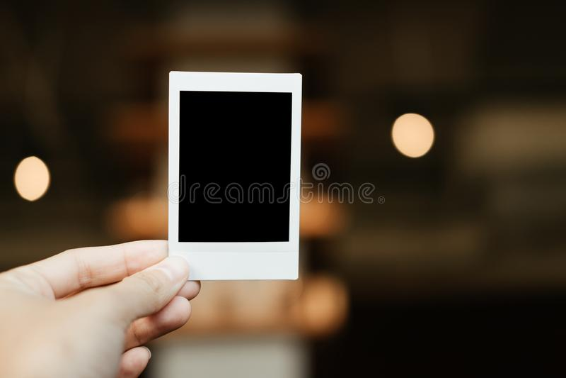 Front View mano de la mujer joven que sostiene la película polaroid en blanco HAV fotografía de archivo