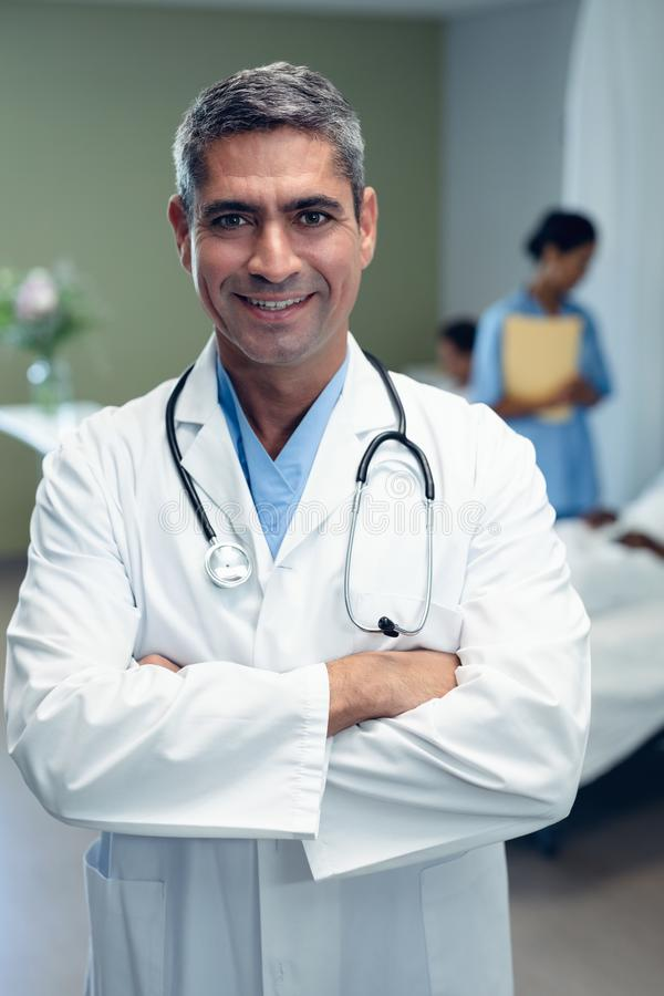 Male doctor standing with arms crossed in the ward at hospital stock image
