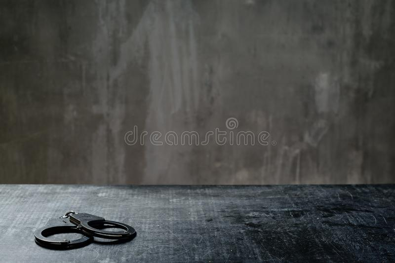 Front view of metal handcuffs on table in interrogation room royalty free stock photography