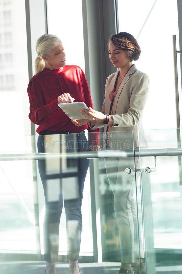 Businesswomen discussing over digital tablet in office building. Front view of mixed race businesswomen discussing over digital tablet in modern office building royalty free stock photos