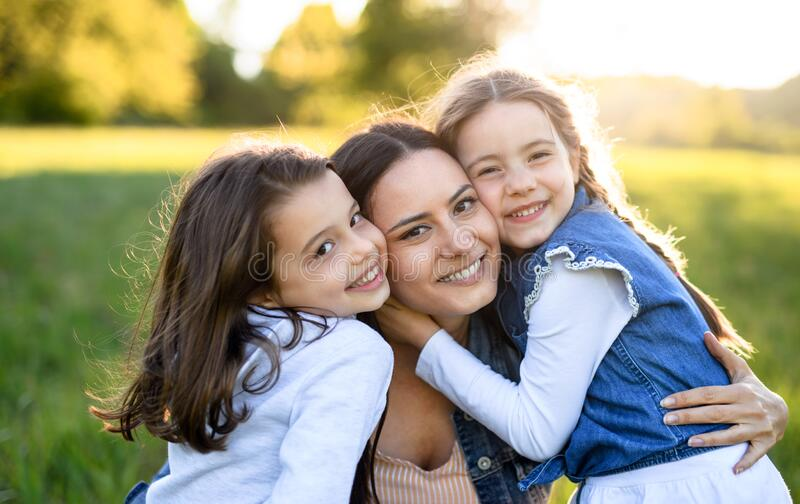 Mother with two small daughters having fun outdoors in spring nature, hugging. royalty free stock image