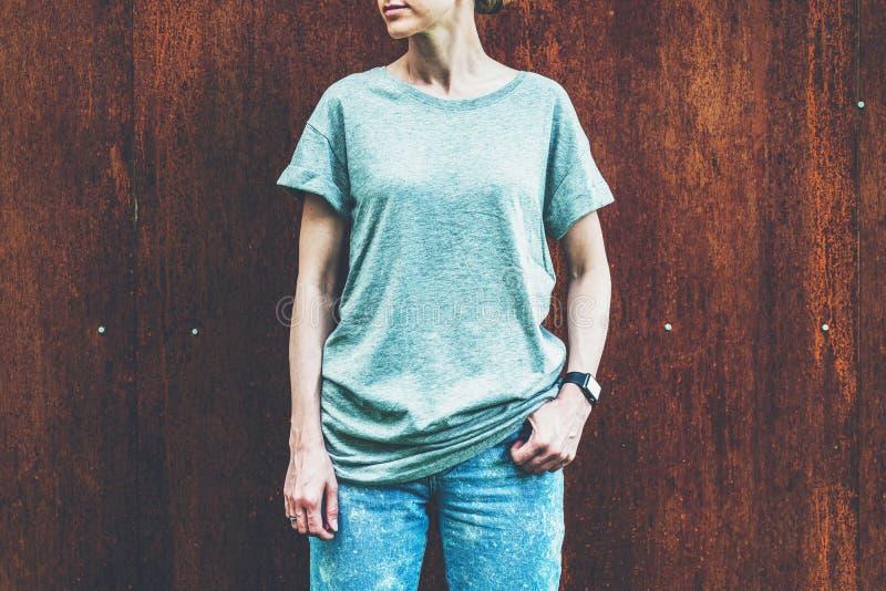 Front View A mulher milenar nova vestida no t-shirt cinzento é suportes contra a parede do metal oxidado imagens de stock royalty free