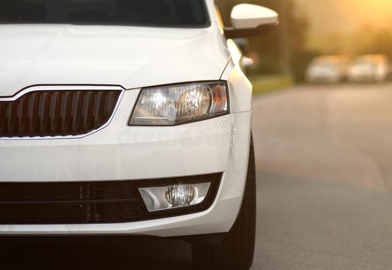 Front view of a new white car, vehicle. New vehicle, car, front view in row on a parking lot in front of a car dealership store, shop. Modern european marque of stock image