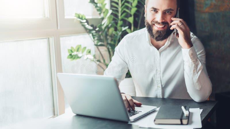 Front View O homem de negócios farpado de sorriso dos jovens está sentando-se no escritório na tabela na frente do portátil, fala imagem de stock royalty free