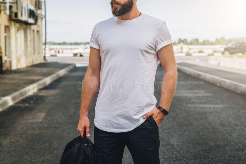 Front View O homem milenar farpado novo vestido no t-shirt branco é suportes na rua da cidade Zombaria acima imagens de stock