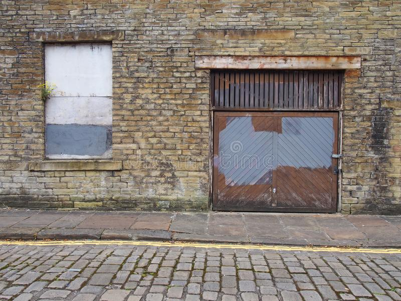 Front view of an old abandoned derelict industrial property on an empty street with boarded up window and dilapidated brick walls royalty free stock images