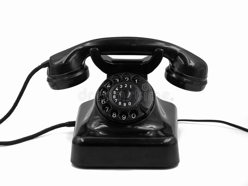Front view of old vintage black rotary dial telephone isolated on white background, retro bakelite phone stock photo