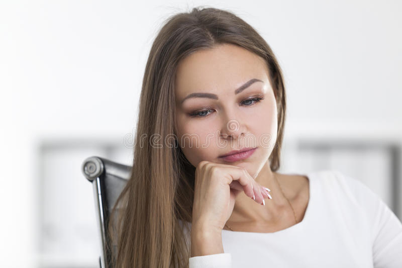 Front view of pensive blond businesswoman, office. Front view of a pensive blond busiensswoman in her office. She is sitting at her desk and looking into stock image