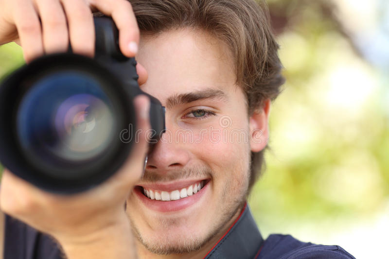 Front view of a photographer photographing with a dslr camera. Showing lens with a green background royalty free stock images