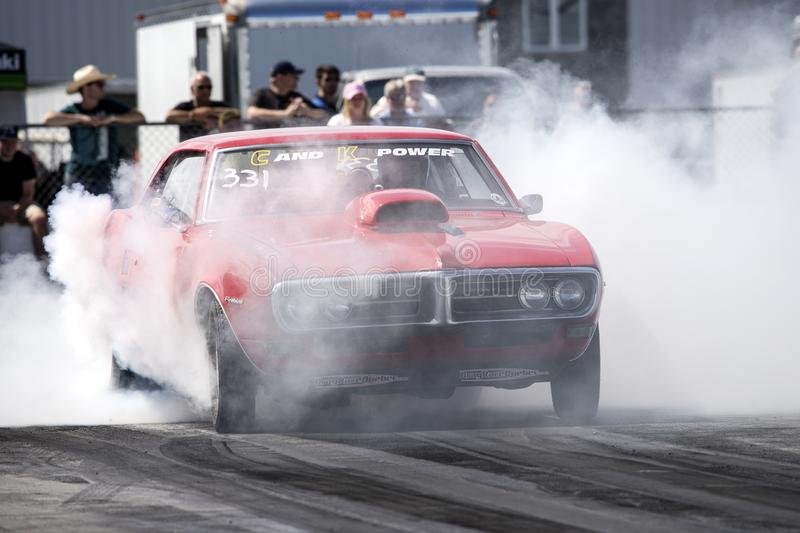 Firebird smoke show. Front view of Pontiac firebird at starting line on the track making a smoke show during the john scotti all out august 17, 2017 royalty free stock photo