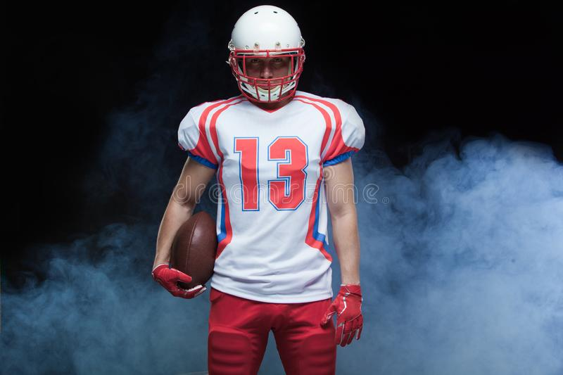 Front view portrait of american football player wearing helmet with ball against white smoke royalty free stock image