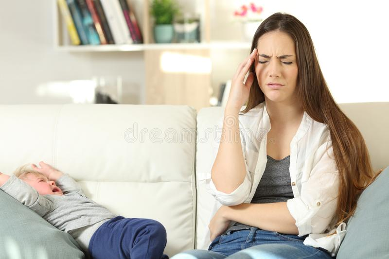 Annoyed mother and baby crying on a couch royalty free stock images