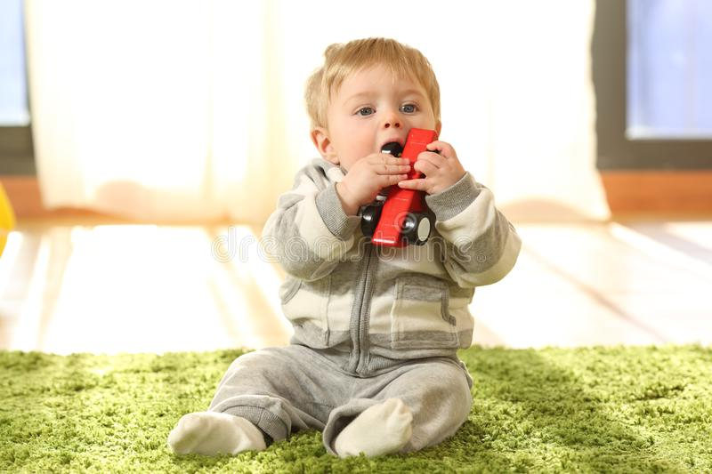 Baby sitting on a carpet biting a toy at home. Front view portrait of a baby sitting on a carpet biting a toy at home stock photo