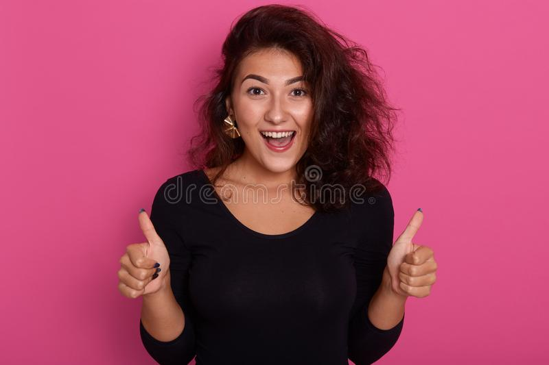 Front view portrait of beautiful young woman giving thumbs up standing isolated over rosy background, Caucasian model smiling stock photography